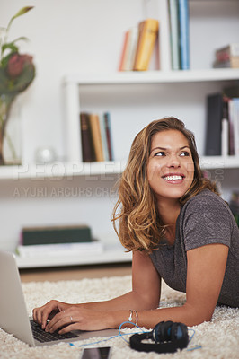 Buy stock photo Shot of a young woman relaxing at home with her laptop