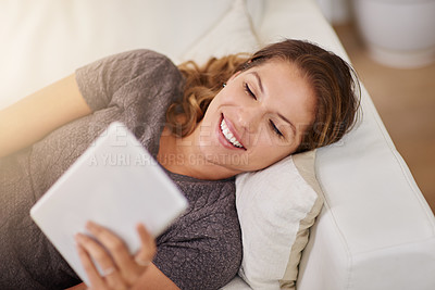 Buy stock photo Shot of a young woman relaxing on the sofa with a digital tablet at home