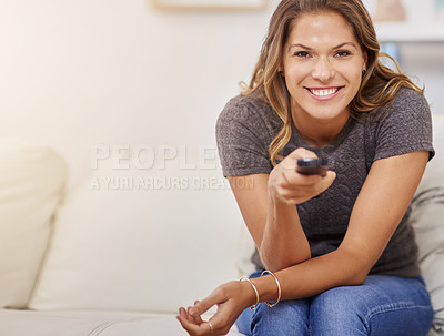 Buy stock photo Shot of a young woman spending a relaxing weekend at home watching tv