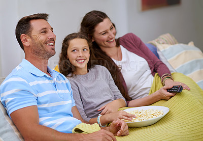 Buy stock photo Cropped shot of a family watching a movie on the sofa