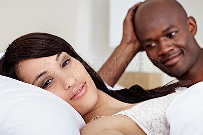 Buy stock photo Portrait of a smiling young couple lying in bed together