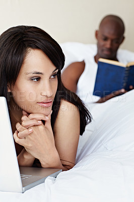Buy stock photo Shot of a young woman lying in bed using a laptop with her husband reading a book in the background
