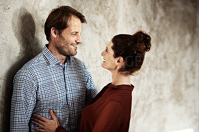 Buy stock photo Shot of an affectionate couple leaning against a wall