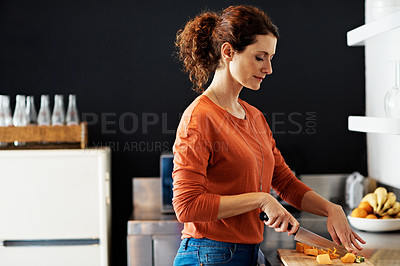 Buy stock photo Shot of a woman chopping vegetables in her kitchen
