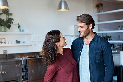 Buy stock photo Shot of an affectionate couple standing arm in arm in their living room