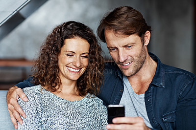 Buy stock photo Shot of a happy couple sitting on their sofa reading a text message
