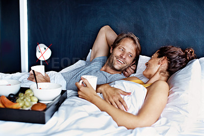 Buy stock photo Shot of a content couple lying in bed together eating breakfast