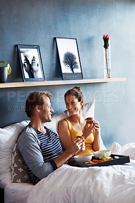 Buy stock photo Shot of a content couple sitting in bed together eating breakfast