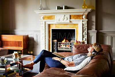 Buy stock photo Shot of a mature woman lying back on her sofa listening to music on a digital tablet