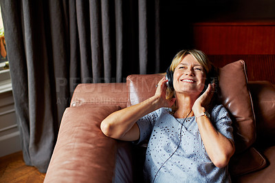 Buy stock photo Shot of a mature woman lying back on her sofa listening to music on headphones