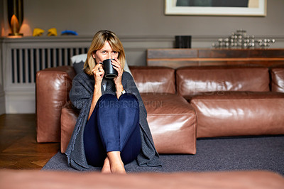 Buy stock photo Shot of a mature woman sitting on her living room floor drinking tea while wrapped in a blanket