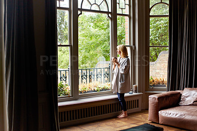 Buy stock photo Shot of a mature woman drinking tea while looking out of her living room window