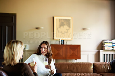 Buy stock photo Shot of two women sitting on a sofa drinking wine and talking