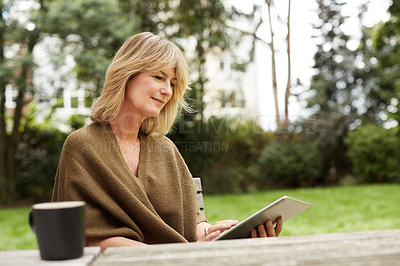 Buy stock photo Shot of a mature woman sitting in her yard drinking tea and using a digital tablet