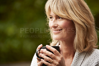 Buy stock photo Shot of a mature woman standing in her yard drinking a cup of coffee
