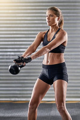 Buy stock photo Cropped shot of a young woman working out with a kettle bell at the gym