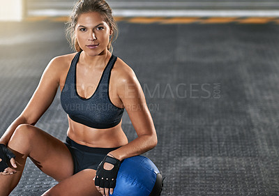 Buy stock photo Cropped portrait of a young woman sitting beside a kettle bell after her workout