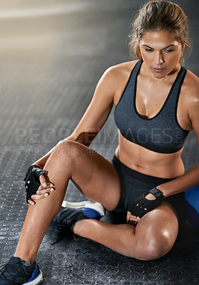 Buy stock photo Full length shot of a young woman sitting beside a kettle bell after her workout