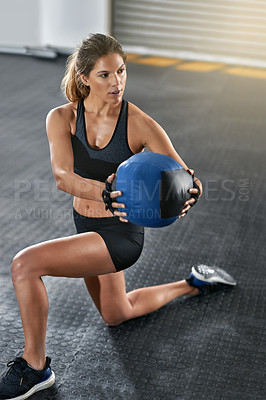 Buy stock photo Full length shot of a young woman working out with a medicine ball at the gym