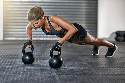 Buy stock photo Full length shot of a young woman working out with kettle bells at the gym