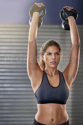 Buy stock photo Cropped shot of a young woman working out with kettle bells at the gym