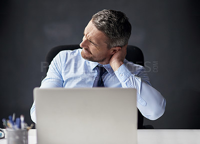 Buy stock photo Cropped shot of a mature businessman running his neck anxiously while working in his office