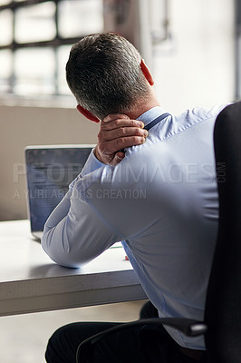 Buy stock photo Rearview shot of a mature businessman running his neck anxiously while working in his office