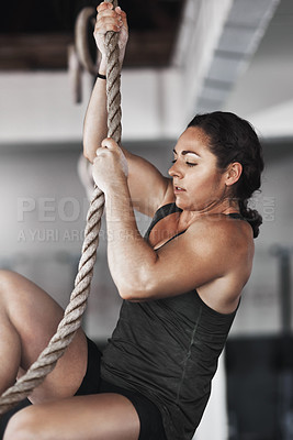 Buy stock photo Cropped shot of a young woman climbing a rope at the gym