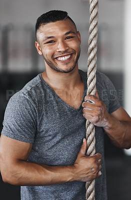 Buy stock photo Cropped portrait of a young man climbing a rope at the gym