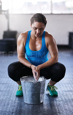 Buy stock photo Full length shot of a young woman putting chalk powder on her hands at the gym