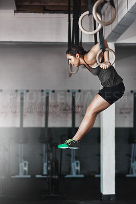 Buy stock photo Full length shot of a young woman working out on the gymnastics rings
