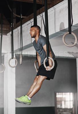 Buy stock photo Full length shot of a young man working out on the gymnastics rings