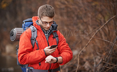 Buy stock photo Shot of a hiker using his phone while looking at his wristwatch