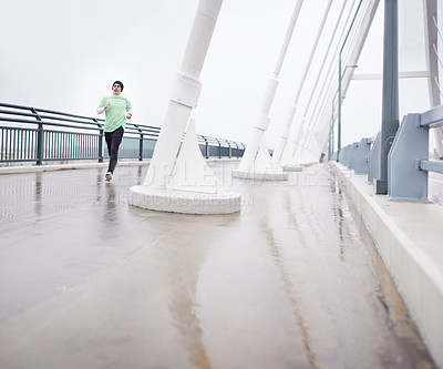 Buy stock photo Shot of a young man out for a run on a wet morning