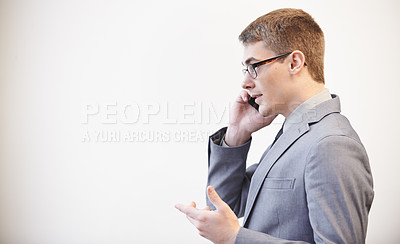 Buy stock photo Studio shot of a young businessman using his cellphone against a grey background
