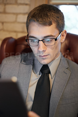 Buy stock photo Cropped shot of a young businessman using his digital tablet