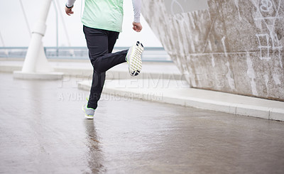 Buy stock photo Cropped shot of a man out for a run on a rainy morning