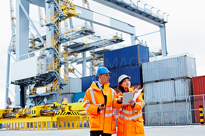 Buy stock photo Shot of two dock workers looking through paperwork while standing in a dockyard