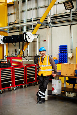 Buy stock photo Portrait of a man in workwear standing by toolboxes in a large industrial building