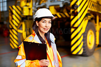 Buy stock photo Shot of a woman in workwear standing in a large industrial building