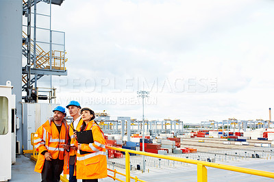 Buy stock photo Shot of three workers talking together while standing on a overhead walkway at a commercial dock
