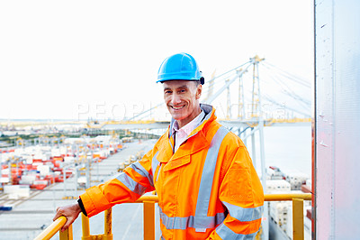 Buy stock photo Portrait of a man in workwear standing on a walkway looking out over at a large commercial dock