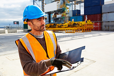 Buy stock photo Shot of man reading paperwork while standing on a large commercial dock