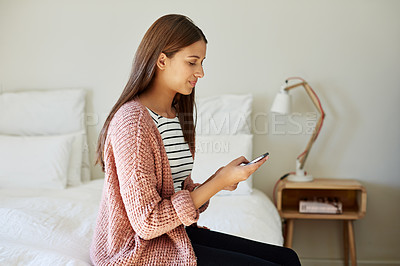 Buy stock photo Shot of a young woman sitting on her bed using a cellphone