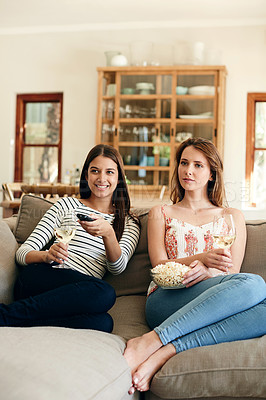 Buy stock photo Shot of two friends drinking wine and eating popcorn while watching a movie together on the sofa at home