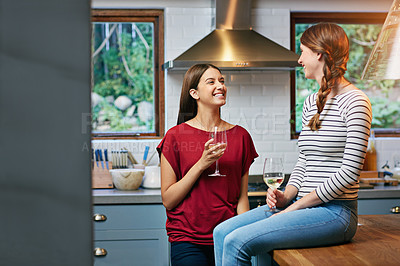 Buy stock photo Shot of two friends drinking wine together in the kitchen