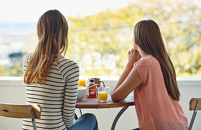 Buy stock photo Rearview shot of two friends eating breakfast together on a balcony