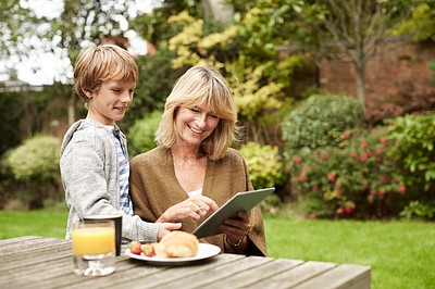 Buy stock photo Shot of a grandmother and her grandson sitting at a table in her yard using a digital tablet