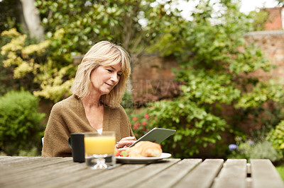 Buy stock photo Shot of a mature woman sitting in her yard having breakfast and using a digital tablet