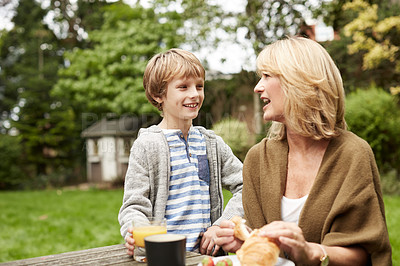 Buy stock photo Shot of a grandmother and her grandson have lunch at a table in her yard